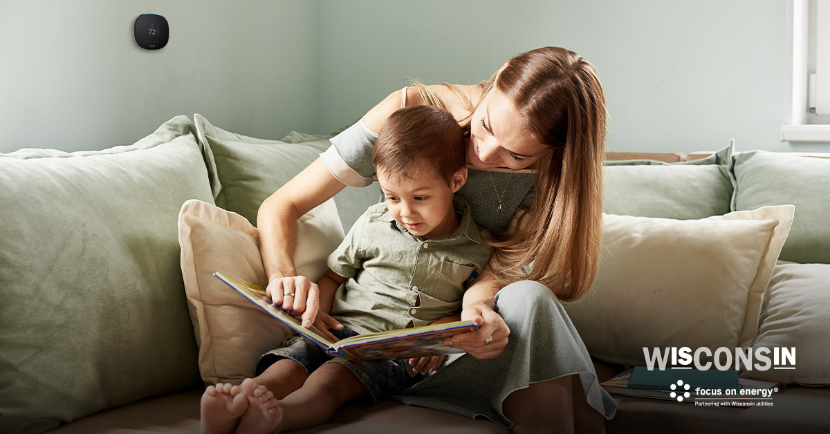 A mother and son read a book together on the couch. A smart thermostat can be seen on the wall in the background.