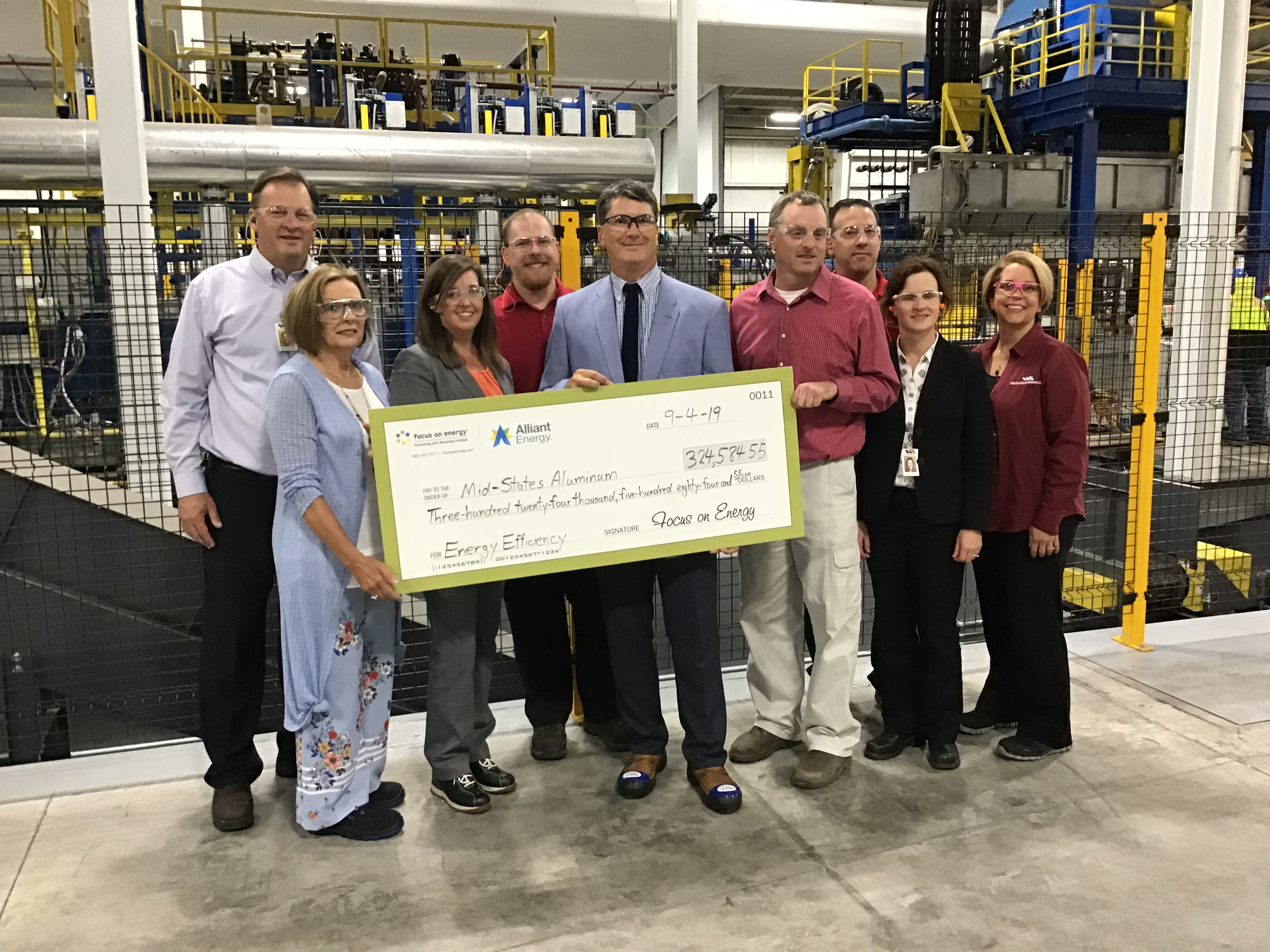 A group of formally-dressed people wearing safety goggles gathers inside an industrial building, holding a large presentation check.