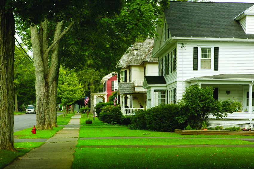 Image of a neighborhood street with one white, two story home featured. There is a large green lawn and a sidewalk with trees to the left.