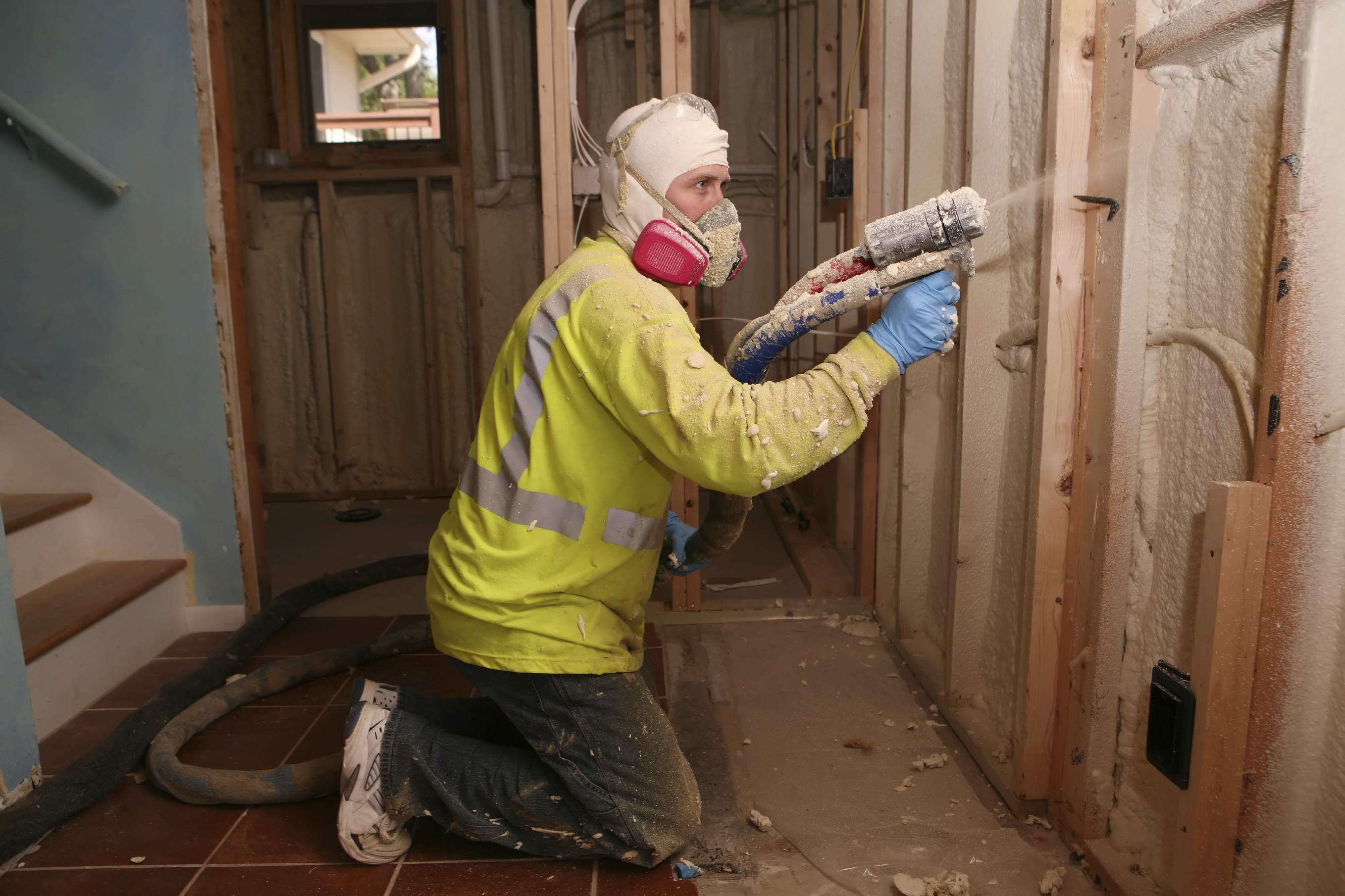 A worker in protective gear installs spray foam insulation in a home that is under construction.