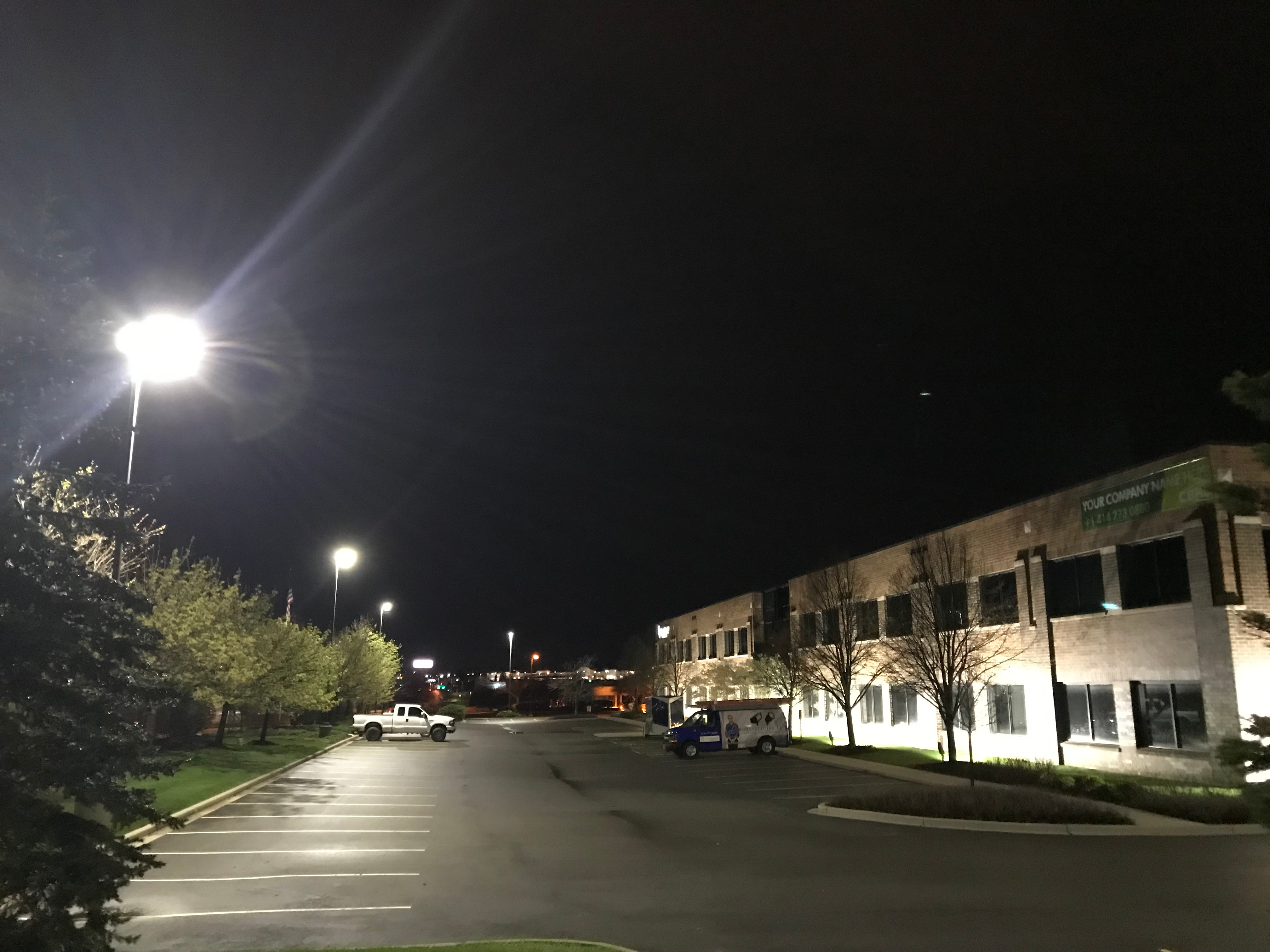 Exterior shot of a commercial building at night, including the building's parking lot.